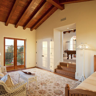Mid-sized tuscan guest medium tone wood floor bedroom photo in Santa Barbara with yellow walls and no fireplace