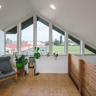 Diseño de dormitorio tipo loft, moderno, de tamaño medio, con paredes blancas y suelo de contrachapado