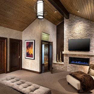 Modelo de dormitorio principal, contemporáneo, de tamaño medio, con paredes grises, moqueta, chimenea lineal, marco de chimenea de piedra y suelo beige