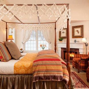 Стильный дизайн: спальня в классическом стиле с бежевыми стенами, стандартным камином, фасадом камина из кирпича и телевизором - последний тренд