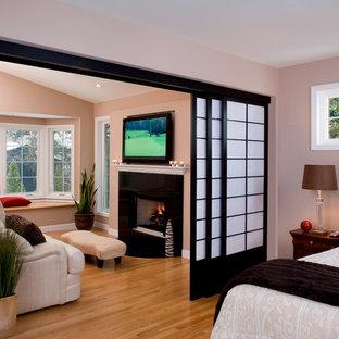 シカゴの広いアジアンスタイルのおしゃれな主寝室 (ベージュの壁、淡色無垢フローリング、標準型暖炉、石材の暖炉まわり、茶色い床) のインテリア