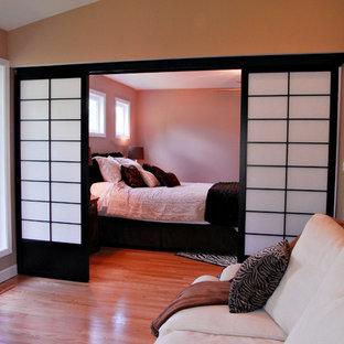 Imagen de dormitorio principal, de estilo zen, grande, con paredes beige, suelo de madera clara, chimenea tradicional, marco de chimenea de piedra y suelo marrón