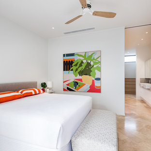 This is an example of a tropical master bedroom in Perth with white walls.