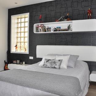 Modelo de dormitorio tipo loft, minimalista, de tamaño medio, con paredes negras y suelo de madera en tonos medios