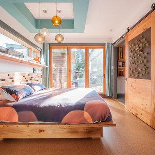 Foto di una camera padronale moderna di medie dimensioni con pareti bianche, pavimento in sughero e nessun camino