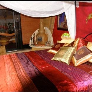 Modelo de dormitorio tipo loft, de estilo zen, de tamaño medio, con paredes rojas, suelo de baldosas de terracota, chimenea de esquina, marco de chimenea de piedra y suelo naranja