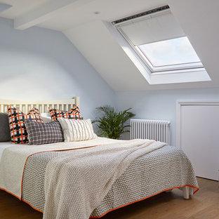 Cette photo montre une chambre d'amis chic avec un mur bleu, un sol en bois brun et un sol marron.