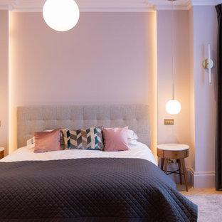 Exemple d'une chambre parentale tendance de taille moyenne avec un mur rose, un sol en bois clair et un sol beige.
