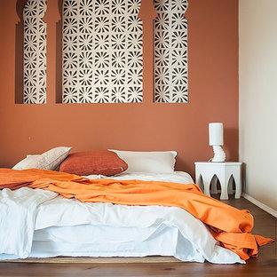 Modelo de dormitorio principal, de estilo zen, de tamaño medio, con parades naranjas y suelo de madera clara