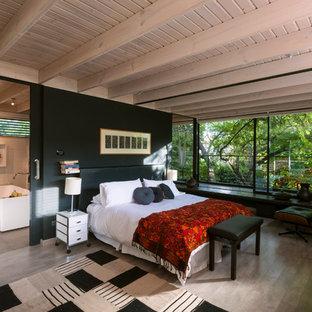 Foto di una grande camera matrimoniale minimal con pareti nere, pavimento in laminato e nessun camino