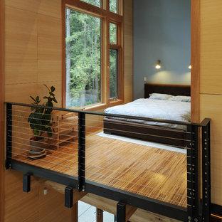 Ejemplo de dormitorio tipo loft, actual, de tamaño medio, sin chimenea, con suelo de bambú y paredes azules