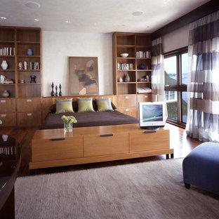 Esempio di una camera da letto minimalista con pareti bianche e pavimento in legno massello medio