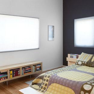 Immagine di una camera matrimoniale minimalista di medie dimensioni con pareti nere e pavimento in bambù