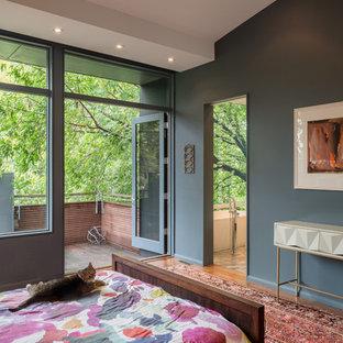 Diseño de dormitorio principal, actual, pequeño, con paredes grises, suelo de madera en tonos medios, chimenea de doble cara, marco de chimenea de piedra y suelo marrón