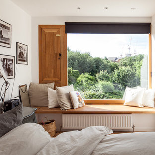 Photo of a classic guest bedroom in London with white walls and brown floors.