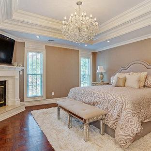 Ejemplo de dormitorio principal, tradicional, de tamaño medio, con paredes beige, suelo de madera oscura, chimenea de esquina y marco de chimenea de ladrillo