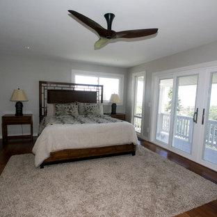 Modelo de dormitorio principal, tropical, grande, sin chimenea, con paredes grises, marco de chimenea de yeso y suelo de madera en tonos medios
