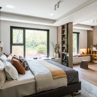 Photo of a contemporary master bedroom in London with white walls, medium hardwood flooring and brown floors.