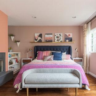 Modelo de dormitorio principal, tradicional renovado, con paredes rosas, suelo de madera en tonos medios, chimenea de esquina, marco de chimenea de yeso y suelo marrón
