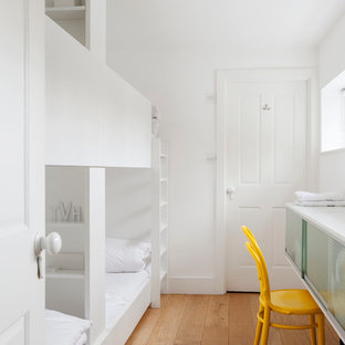 This is an example of a small scandinavian guest bedroom in London with white walls, medium hardwood flooring and no fireplace.