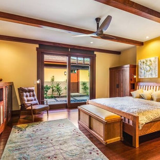 This is an example of a large arts and crafts guest bedroom in Hawaii with orange walls and dark hardwood floors.