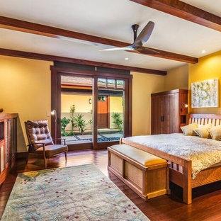 Foto di una grande camera degli ospiti american style con pareti arancioni e parquet scuro