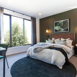 Exemple d'une grand chambre avec moquette tendance avec un mur vert, un sol beige et du lambris.