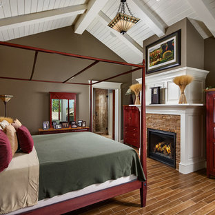Design ideas for an arts and crafts master bedroom in Denver with brown walls, a standard fireplace, a stone fireplace surround and brown floor.