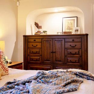 Ejemplo de dormitorio principal, tradicional renovado, de tamaño medio, con paredes beige y chimeneas suspendidas