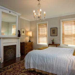 На фото: хозяйские спальни в стиле модернизм с бежевыми стенами, темным паркетным полом, стандартным камином и фасадом камина из дерева