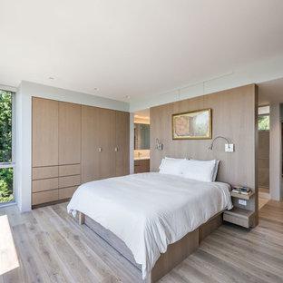 Réalisation d'une chambre parentale design avec un sol en bois clair et aucune cheminée.