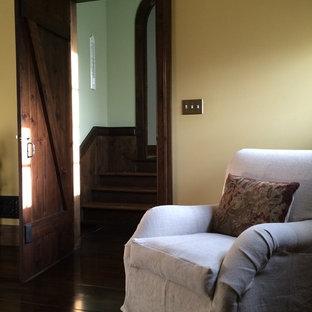Foto de dormitorio principal, campestre, grande, con paredes amarillas y suelo de madera oscura
