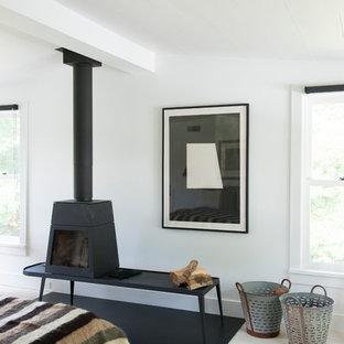 На фото: хозяйская спальня среднего размера в стиле ретро с белыми стенами, деревянным полом и печью-буржуйкой