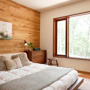 Imagen de dormitorio principal, actual, de tamaño medio, con suelo de madera en tonos medios y paredes blancas