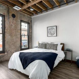Ejemplo de habitación de invitados ladrillo, urbana, de tamaño medio, sin chimenea, con paredes beige, suelo de madera clara, suelo marrón y ladrillo