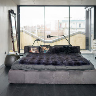 This is an example of a medium sized industrial bedroom in London with white walls, dark hardwood flooring and no fireplace.