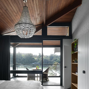 Large contemporary master bedroom in Sydney with white walls, ceramic floors, no fireplace and grey floor.