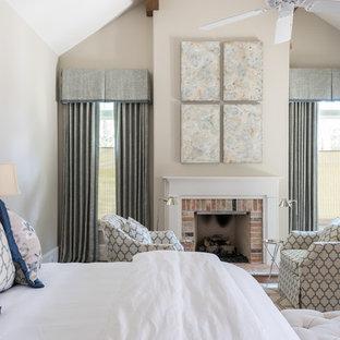 Esempio di una camera matrimoniale tradizionale di medie dimensioni con pareti beige, camino classico, cornice del camino in mattoni e pavimento in legno massello medio