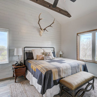 Inspiration for a rustic medium tone wood floor and brown floor bedroom remodel in Oklahoma City with white walls
