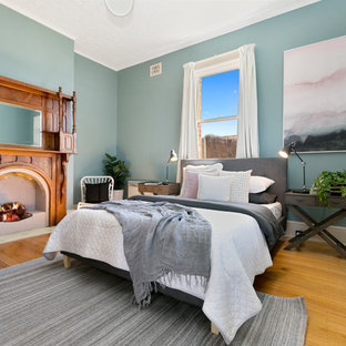 Inspiration for a transitional bedroom in Hobart with blue walls, medium hardwood floors, a standard fireplace, a wood fireplace surround and brown floor.