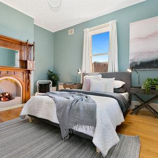 ホバートのトランジショナルスタイルのおしゃれな寝室 (青い壁、無垢フローリング、標準型暖炉、木材の暖炉まわり、茶色い床) のレイアウト