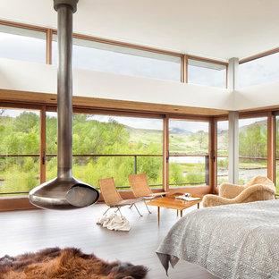 Modelo de dormitorio moderno con suelo de madera clara y estufa de leña
