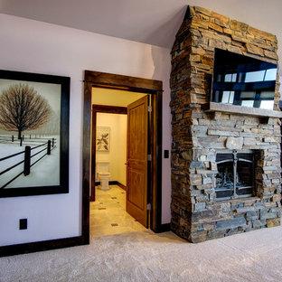 Diseño de dormitorio principal, rústico, grande, con paredes púrpuras, moqueta, chimenea tradicional y marco de chimenea de piedra