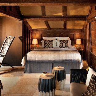Modelo de dormitorio principal, tropical, de tamaño medio, sin chimenea, con paredes marrones y suelo de travertino