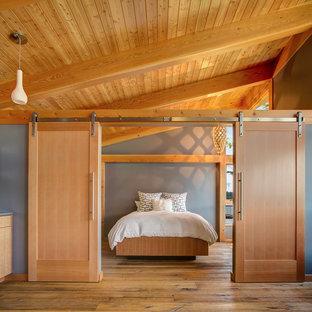 Diseño de dormitorio principal, rural, grande, sin chimenea, con paredes grises, suelo de madera en tonos medios y suelo marrón