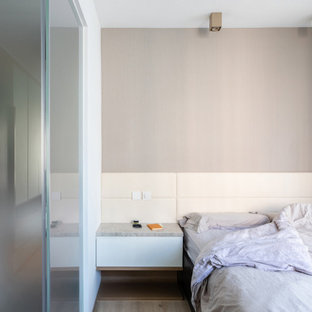 Photo of a small modern master bedroom in Hong Kong with multi-coloured walls, limestone floors, no fireplace and brown floor.