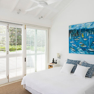Inspiration for a beach style guest bedroom in Sydney with white walls, carpet and beige floor.