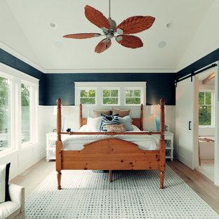 Foto de dormitorio principal, costero, grande, con paredes multicolor, suelo de madera clara y suelo marrón