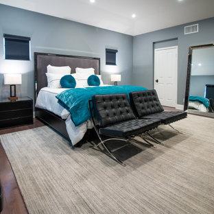 Modelo de dormitorio principal, urbano, de tamaño medio, con paredes grises, suelo de madera oscura, chimenea lineal, marco de chimenea de baldosas y/o azulejos y suelo marrón