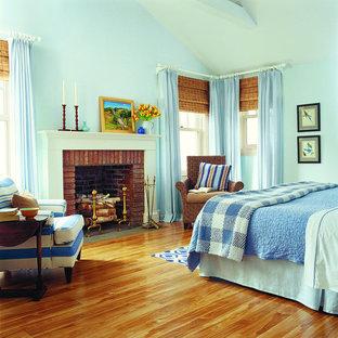 Foto de habitación de invitados de estilo de casa de campo, de tamaño medio, con paredes azules, suelo laminado, chimenea tradicional y marco de chimenea de ladrillo